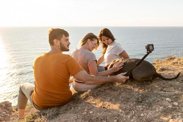 Zijaanzichtvrienden die een selfie aan een kust nemen Gratis Foto