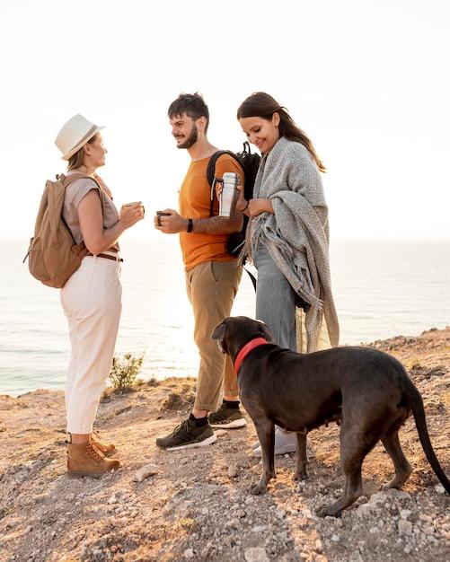 Zijaanzichtvrienden die met een hond reizen Gratis Foto