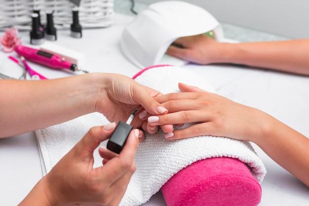 Zijaanzichtvrouw die de manicure van een cliënt doet Premium Foto