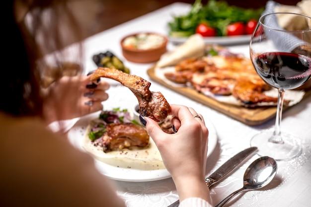 Zijaanzichtvrouw die de rib van het kebablam met een glas rode wijn eet Gratis Foto