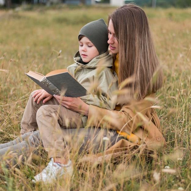 Zijaanzichtvrouw die een boek in openlucht lezen aan zijn zoon Gratis Foto