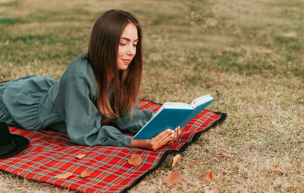 Zijaanzichtvrouw die een boek op een picknickkleed leest Gratis Foto