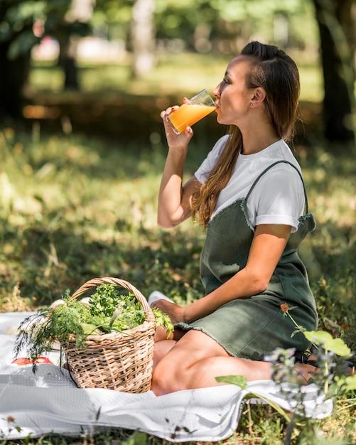 Zijaanzichtvrouw die een picknick met gezonde snacks heeft Gratis Foto