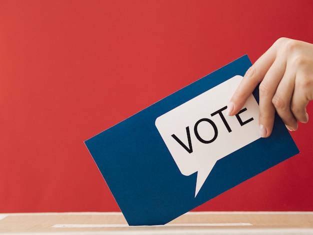Zijaanzichtvrouw die een stemmingskaart in een doos met rode achtergrond zetten Gratis Foto