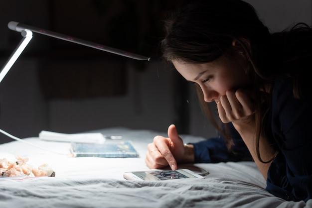 Zijaanzichtvrouw die in donkere slaapkamer werken. Gratis Foto