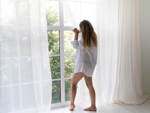 Zijaanzichtvrouw die uit het venster kijkt Gratis Foto
