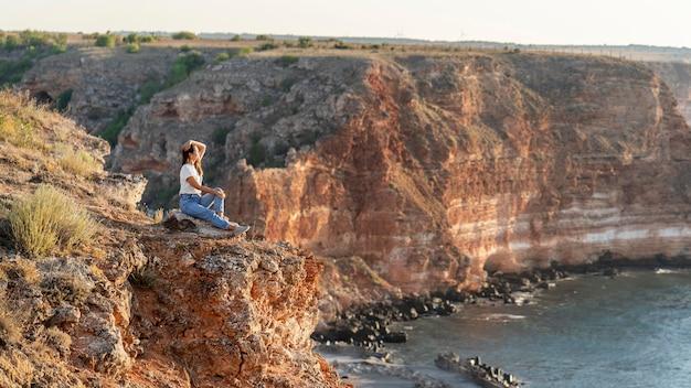 Zijaanzichtvrouw die van het uitzicht met exemplaarruimte geniet Gratis Foto