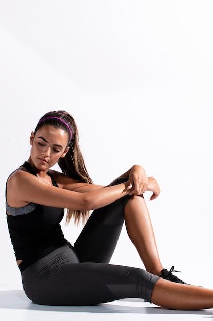 Zijaanzichtvrouw in de zitting van het gymnastiekkostuum Gratis Foto