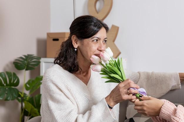 Zijaanzichtvrouw met bloemen Gratis Foto