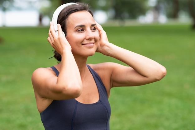 Zijaanzichtvrouw met hoofdtelefoons in openlucht Gratis Foto