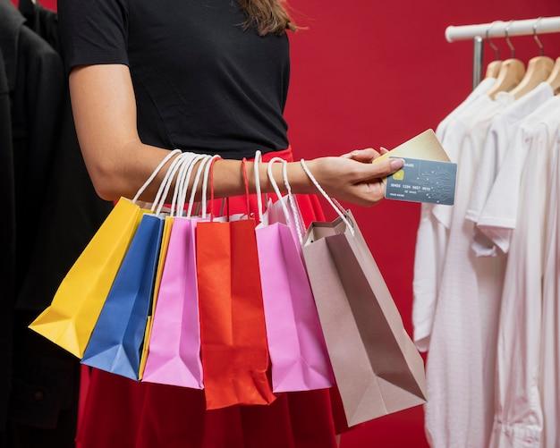 Zijaanzichtvrouw met kleurrijke zakken bij het winkelen Gratis Foto