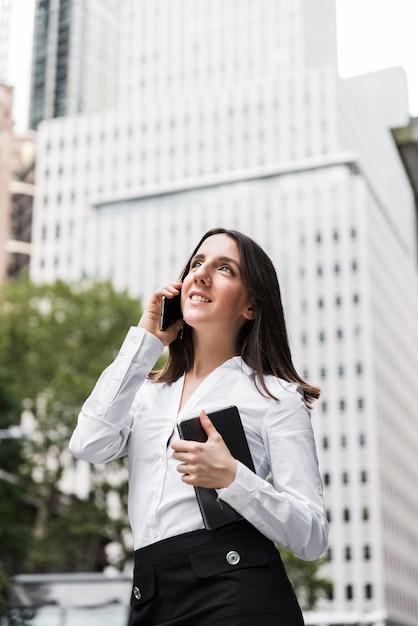 Zijaanzichtvrouw met tablet die op de telefoon spreken Gratis Foto
