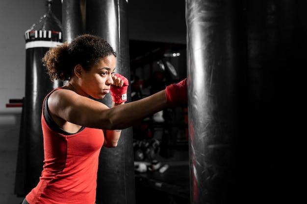 Zijdelings atletische vrouw opleiding in bokscentrum Gratis Foto