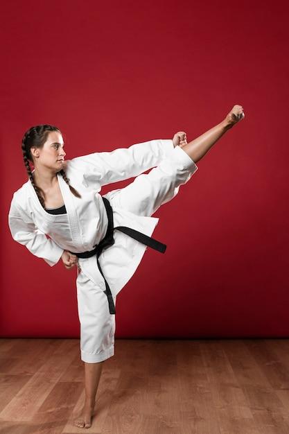 Zijdelings karatevrouw in traditionele witte kimono op rode achtergrond Gratis Foto