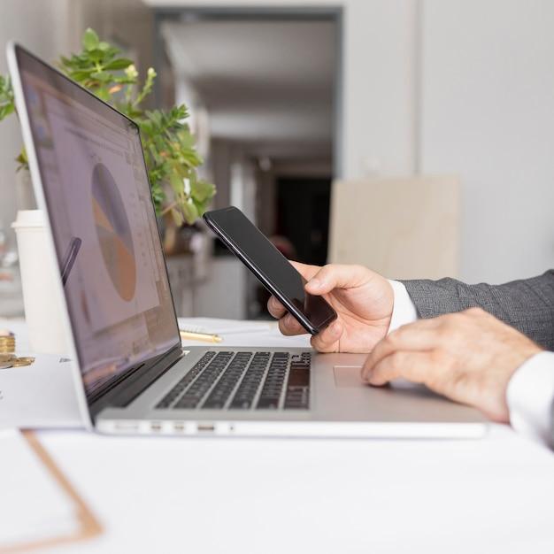 Zijdelings mens die bij zijn laptop werkt Gratis Foto