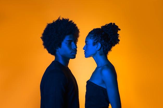 Zijdelings paar met oranje achtergrond Premium Foto