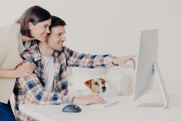 Zijdelings schot van de moderne computer van de gelukkige familie om online te winkelen Premium Foto