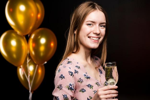 Zijdelings smileyvrouw die een glas champagne houdt Gratis Foto