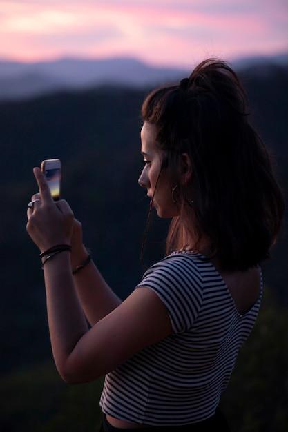 Zijdelings vrouw die een foto met haar telefoon neemt Gratis Foto