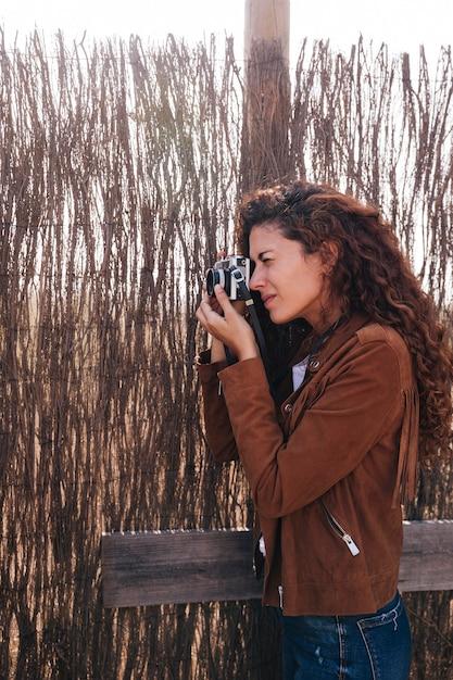 Zijdelings vrouw die foto's neemt Gratis Foto