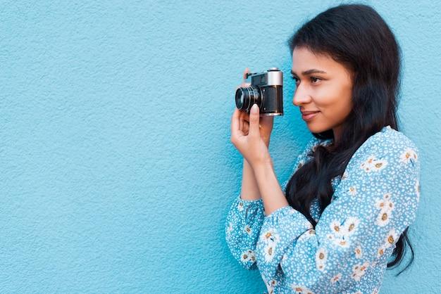 Zijdelings vrouw die haar camerafoto bekijkt Gratis Foto