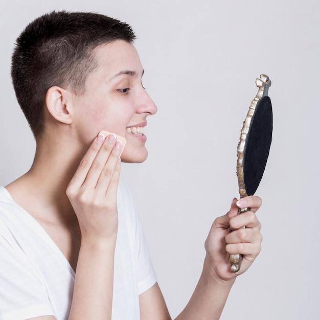 Zijdelings vrouw die haar gezicht schoonmaakt terwijl het kijken in de spiegel Gratis Foto