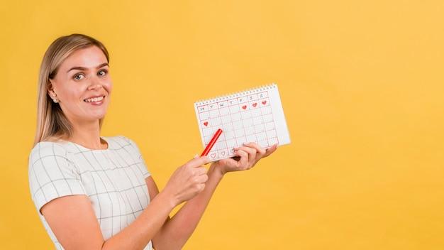Zijdelings vrouw die haar menstruatiekalender toont Gratis Foto