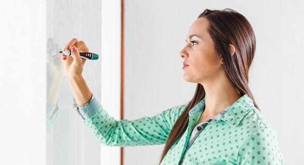 Zijdelings vrouw die op whiteboard schrijft Gratis Foto