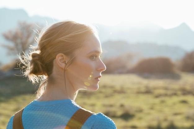 Zijprofiel jonge vrouw in zonlicht Gratis Foto