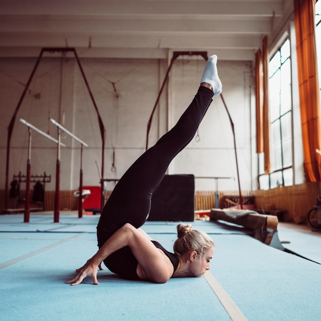 Zijwaarts blonde vrouw training voor olympische gymnastiek Gratis Foto