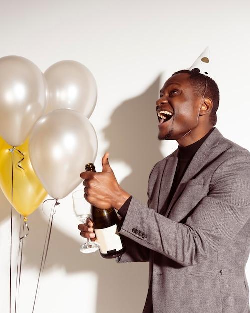 Zijwaarts gelukkige man die een fles champagne opent Gratis Foto