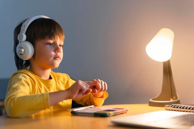 Zijwaarts kind dat virtuele cursussen volgt Gratis Foto