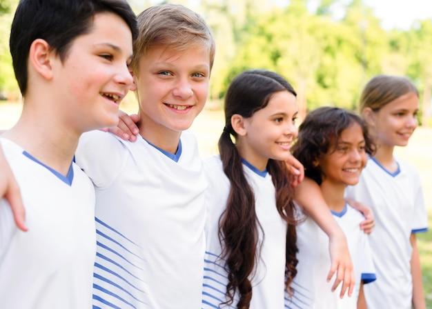 Zijwaarts kinderen in sportkleding houden elkaar vast Gratis Foto