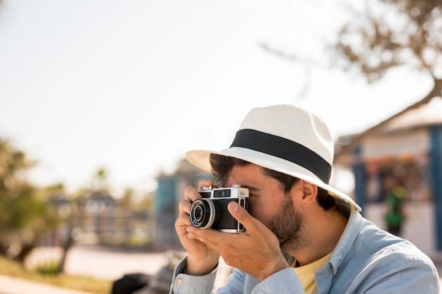 Zijwaarts man die foto's neemt Gratis Foto