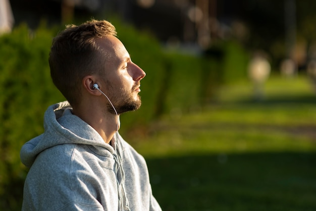Zijwaarts man luisteren naar muziek tijdens het mediteren Gratis Foto