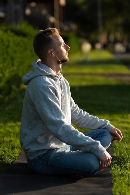 Zijwaarts man mediteren op het strand Gratis Foto