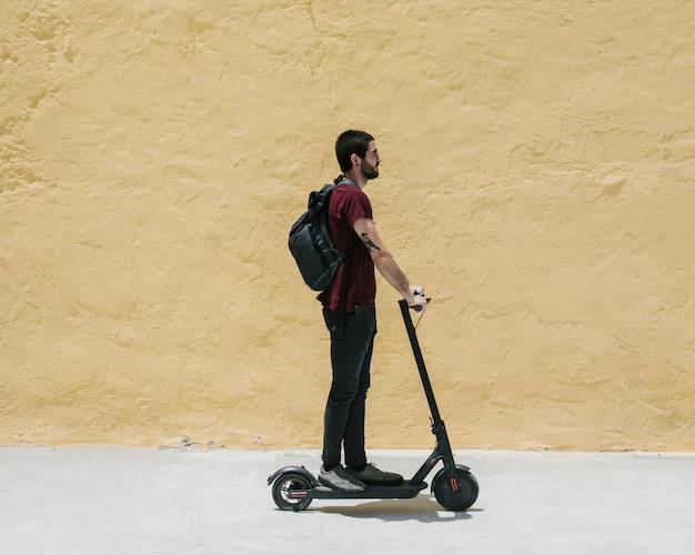Zijwaarts rijdende man op een e-scooter Gratis Foto