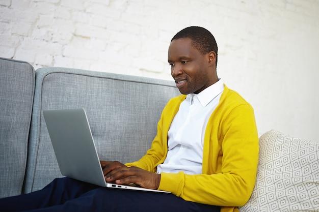 Zijwaarts schot van aantrekkelijke getalenteerde mannelijke copywriter met een donkere huidskleur in stijlvolle slijtage zittend op de bank thuis met draagbare computer op schoot, toetsenbord nieuw artikel voor online internetmagazine Gratis Foto