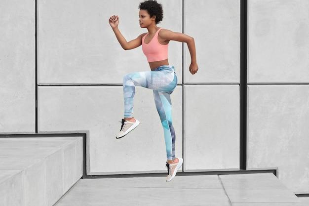 Zijwaarts schot van atletische vrouw kijkt vooruit, rent de trap op, wil afvallen, heeft hoogspringen, draagt sportkleding, overwint uitdaging, fotografeert in beweging, verbrandt vet in lichaam. oefenen Gratis Foto