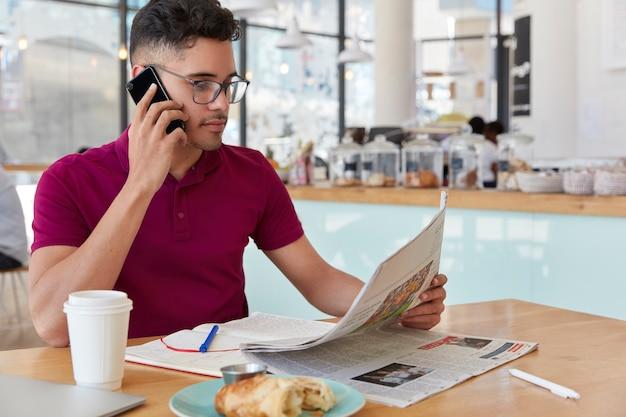 Zijwaarts schot van geconcentreerde ondernemer leest zakenkrant, voert telefoongesprek, werkt op afstand vanuit een coffeeshop, praat via mobiel, drinkt afhaalkoffie, eet een dessert. massamedia concept Gratis Foto