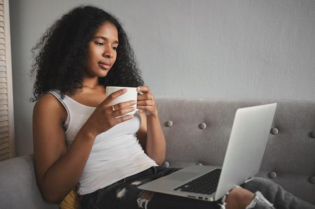 Zijwaarts schot van modieuze aantrekkelijke jonge donkere vrouw in gescheurde spijkerbroek ontspannen op de bank met draagbare computer op haar schoot, koffie drinken en favoriete tv-serie online kijken Gratis Foto