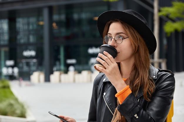 Zijwaarts schot van peinzende jong meisje heeft koffiepauze na een wandeling door de stad, houdt smartphone vast, controleert e-mailbox, gericht op afstand Gratis Foto