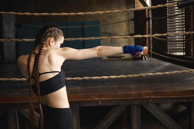 Zijwaarts schot van vastberaden serieuze jonge vrouw met sterke gespierde armen en twee vlechten die lucht voor haar slaan alsof ze boksen tegen een onzichtbare tegenstander Gratis Foto