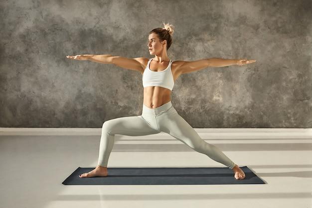 Zijwaarts volledig beeld van aantrekkelijke gespierde jonge vrouw die hatha yoga beoefent in de sportschool, blootsvoets op de mat in virabhadrasana 2 of warrior two pose, met geconcentreerde gezichtsuitdrukking Gratis Foto
