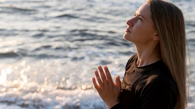 Zijwaarts vrouw mediteren op het strand Gratis Foto