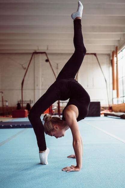 Zijwaartse blonde vrouw die voor gymnastiekkampioenschap opleidt Gratis Foto