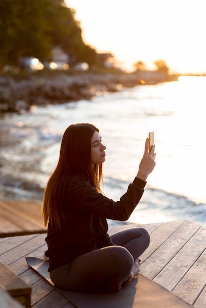 Zijwaartse vrouw die een foto van de zee neemt Gratis Foto