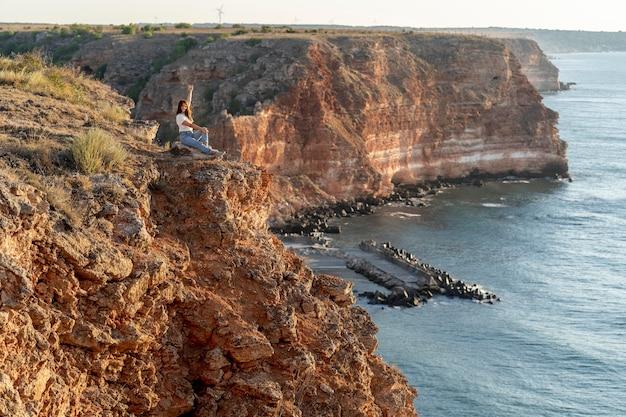 Zijwaartse vrouw die van het uitzicht met exemplaarruimte geniet Gratis Foto