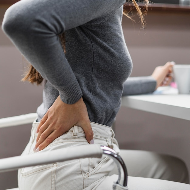Zijwaartse vrouw met rugpijn tijdens het werken vanuit huis Gratis Foto