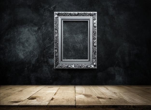 Zilveren antieke foto frame op donkere grunge muur achtergrond met houten tafelblad Premium Foto